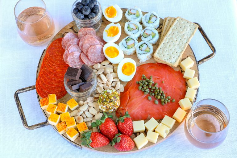 charcuterie board with assorted cheeses, meats, soft boiled eggs, salmon and berries